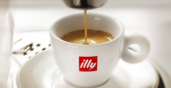 Coffee coming out of the coffee machine into the illy cup